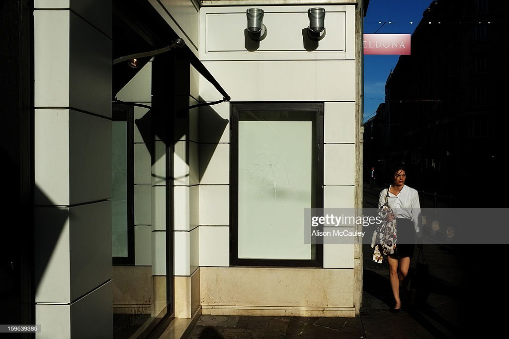 CONTENT] An attractive woman dressed in black and white walks past a black and white building in central Geneva. The late afternoon light is sharp and the shadows are deep.