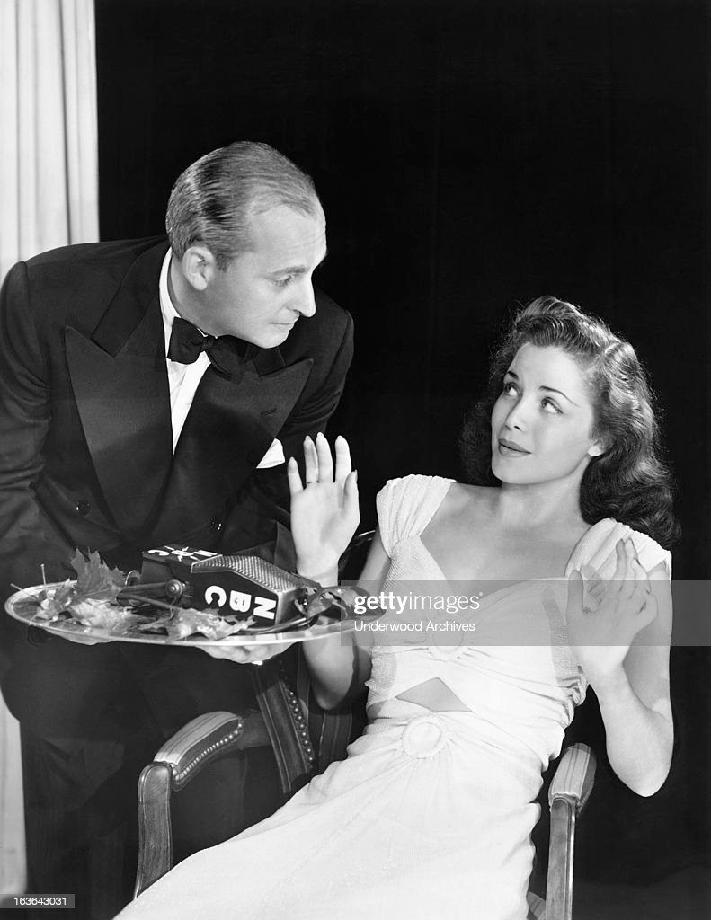 An attractive woman sitting in a chair is offered an NBC microphone on a platter by a waiter, circa 1939.