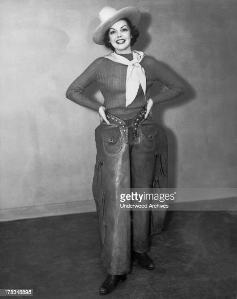 An attractive woman wearing a cowboy hat kerchief boots and chaps stands smiling with her hands on her hips c 1940