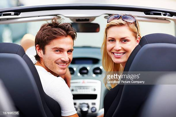 An attractive, young couple in car giving you a smile