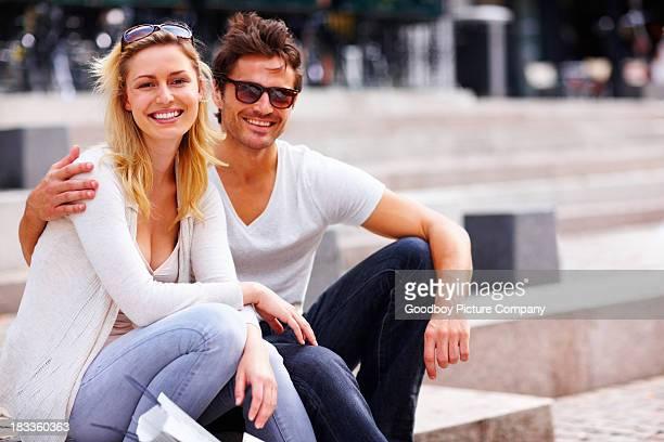 Ein attraktives Junges Paar sitzen zusammen und Lächeln