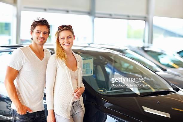 Un'attraente giovane Coppia in piedi con la nuova auto in esposizione