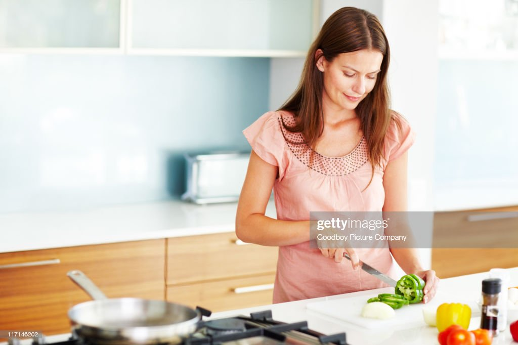 An attractive young female cooking in the kitchen : Stock Photo