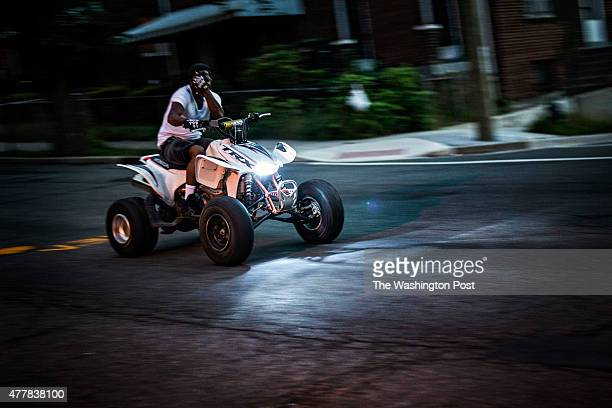 An ATV rider covers his face as he rides past the camera in Northeast Washington Monday June 15 2015