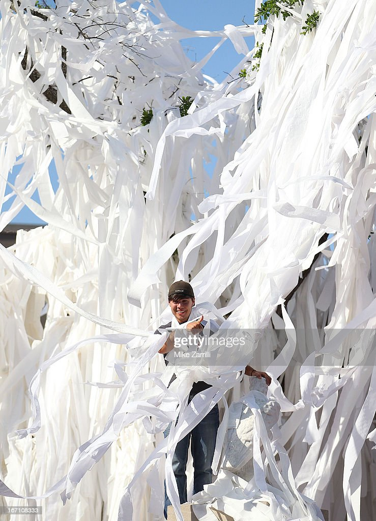 An Auburn fan is inundated with toilet paper while standing in the Auburn Oaks, at the Toomer's Corner Celebration on April 20, 2013 in Auburn, Alabama.