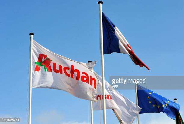 An Auchan's flag is seen near a French national flag and an European flag at the entrance of the groupe Auchan headquarters in Croix northern France...