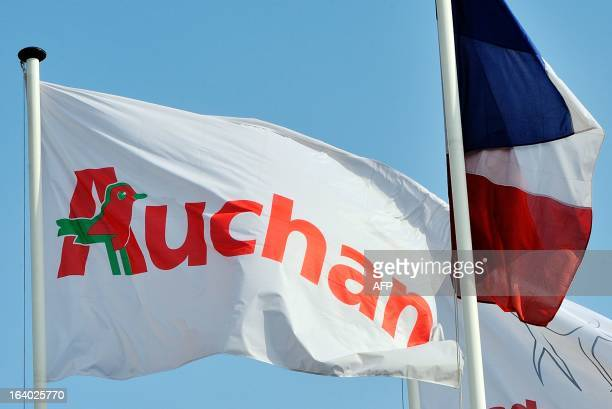 An Auchan's flag is seen near a French national flag at the entrance of the groupe Auchan headquarters in Croix northern France on March 19 2013 AFP...