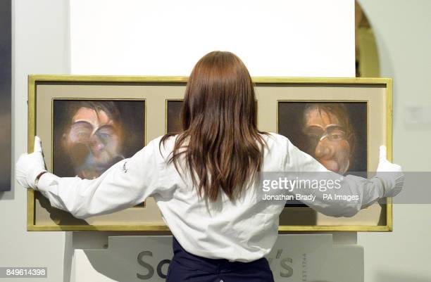 An auction assistant places Francis Bacon's 'Three Studies for a Self Portrait' on display during the Sotheby's London Evening Sale of Contemporary...