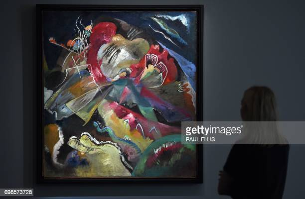 An auction house employee looks at Russian artist Wassily Kandinsky's oil painting 'Bild mit weissen Linien' estimated to fetch in excess of 35...
