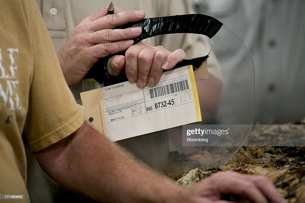 An auction participant waits to write down the buyer of a tobacco bale during an auction at the Old Belt Tobacco Sales warehouse in Rural Hall, North Carolina, U.S., on Tuesday, Aug. 20, 2013. President Barack Obama's proposal in April to raise federal excise taxes on cigarettes by about 93%, to $1.95 a pack, is not likely to gain political support, due in part to weak consumer spending amid sluggish wage growth in recent years. Photographer: Andrew Harrer/Bloomberg via Getty Images