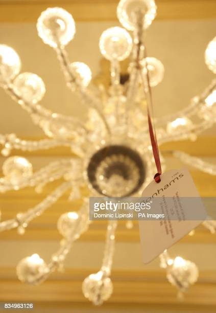 An auction price tag is seen hanging from a Venetian clear glass and gilt decorated chandelier worth around 8 as part of the closing down auction at...