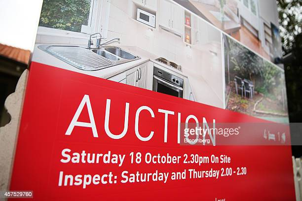 An auction sign stands on display outside a house in the suburb of Waverton in Sydney Australia on Saturday Oct 18 2014 Sydneys median home price...