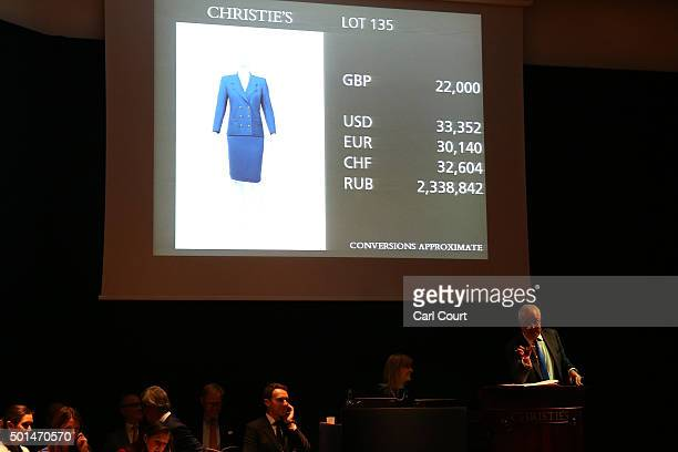 An auctioneer gestures during the sale of an Aquascutum Royal Blue Wool Crepe Suit during the auction for items belonging to late British Prime...