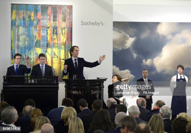 An auctioneer receives bids whilst stood between Gerhard Richter's works 'Wolke' and 'Abstraktes Bild' during the Sotheby's London Evening Sale of...