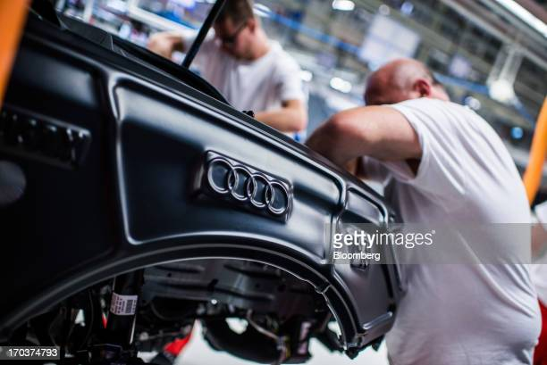 An Audi AG logo sits stamped on the body panel while employees work on the assembly of an Audi A3 automobile on the production line at the company's...