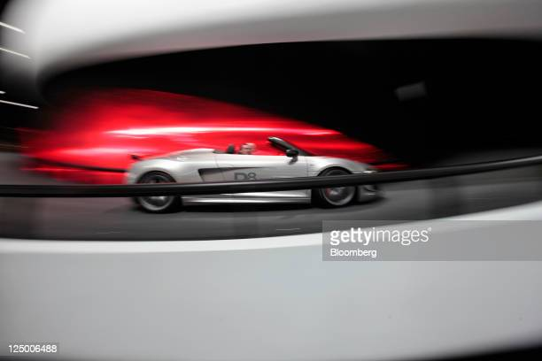 An Audi AG R8 automobile is driven around a test track inside the company's display hall during the Frankfurt Motor Show in Frankfurt Germany on...