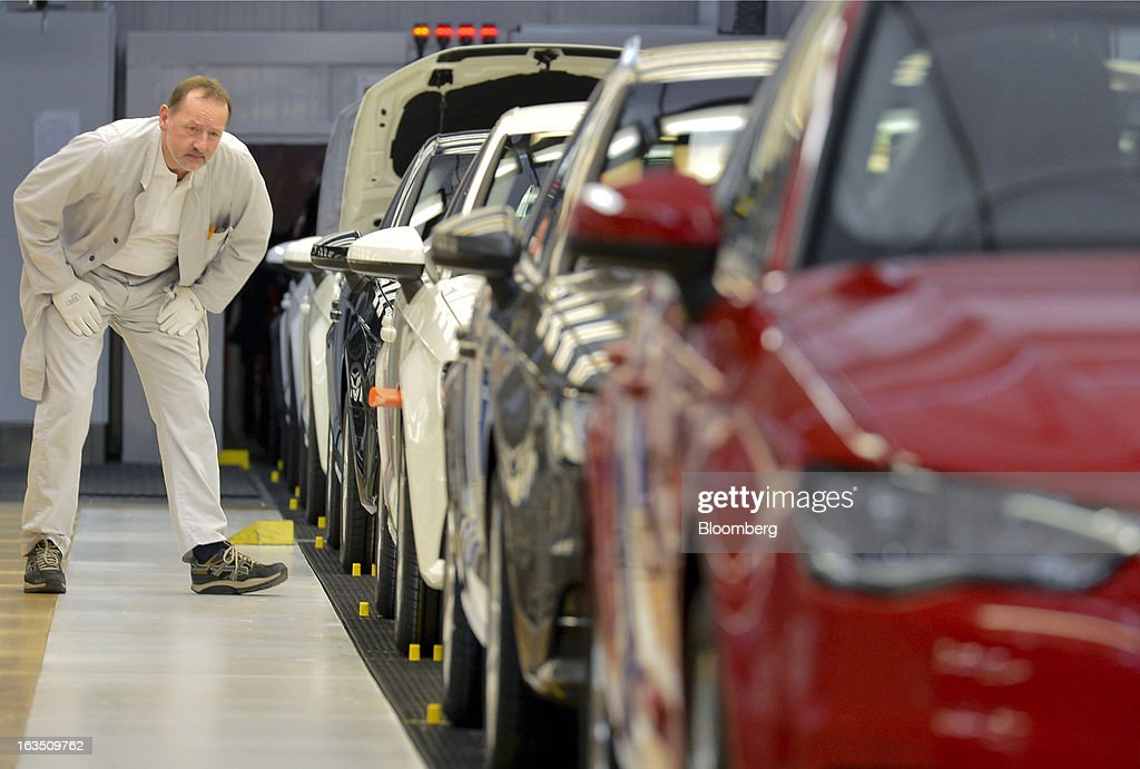 An Audi employee carries out the final inspection on a row of Audi A3 automobiles, produced by Volkswagen AG's Audi brand, as they move along the production line at the company's plant in Ingolstadt, Germany, on Monday, March 11, 2013. Audi, the world's second-largest maker of luxury vehicles, plans to spend 13 billion euros ($17 billion) through 2016 to develop new cars and expand production capacity as it pursues Bayerische Motoren Werke AG's sales lead. Photographer: Guenter Schiffmann/Bloomberg via Getty Images