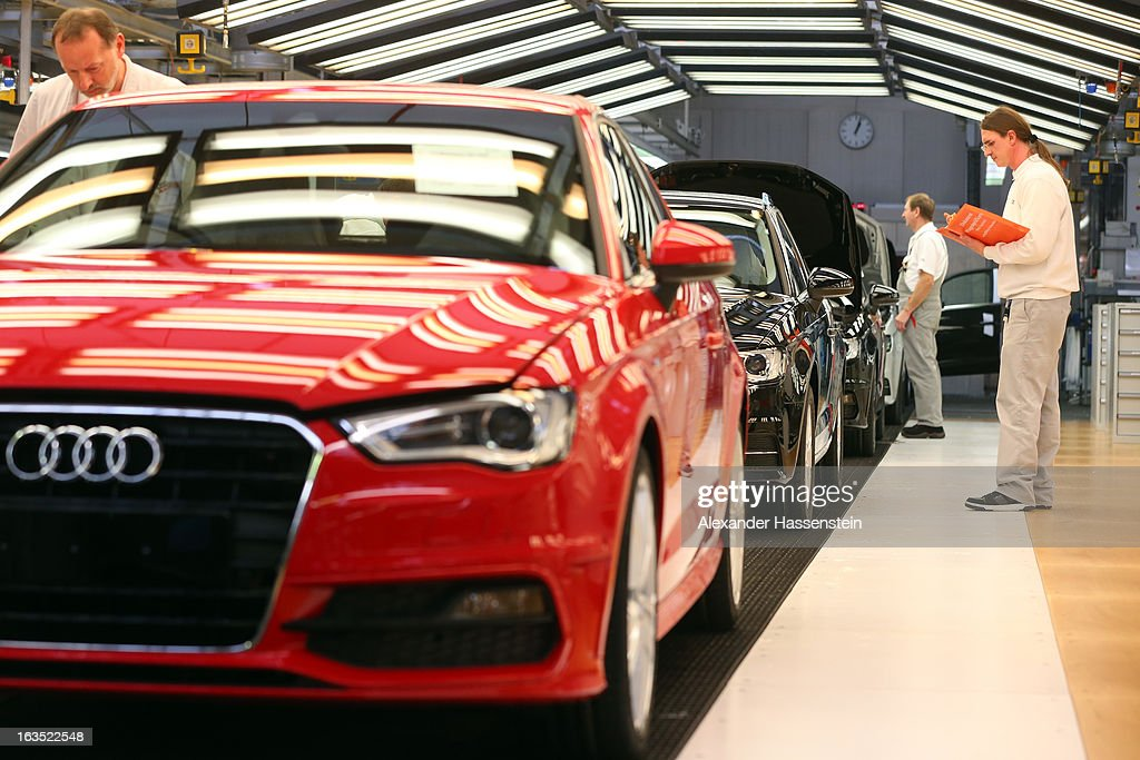 An Audi employee carries out the final inspection on a row of Audi A3 automobiles, produced by Volkswagen AG's Audi brand, as they move along the production line at the company's plant in Ingolstadt, Germany, on Monday, March 11, 2013. Audi is set to spend 13 billion euros ($17 billion) through 2016 to expand and develop new cars pursuing BMW's sales lead.