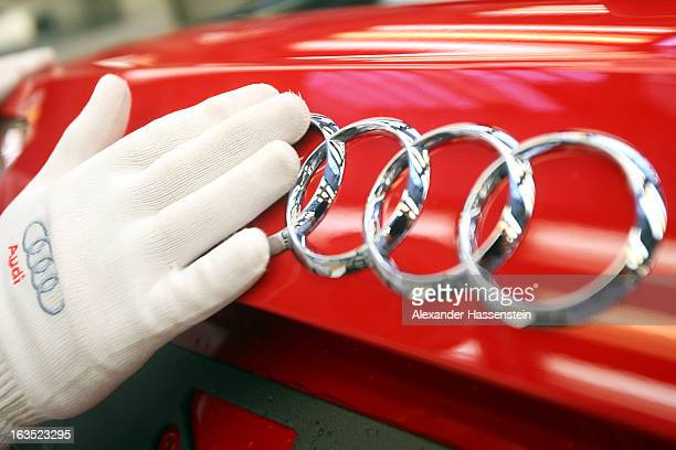 An Audi employee polishes the Audi A3 automobile signs produced by Volkswagen AG's Audi brand as it moves along the production line at the company's...