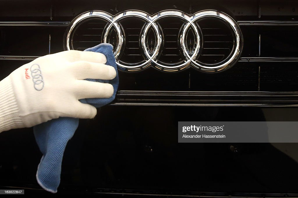 An Audi employee polishes the hood of an Audi A3 automobile, produced by Volkswagen AG's Audi brand, as it moves along the production line at the company's plant in Ingolstadt, Germany, on Monday, March 11, 2013. Audi is set to spend 13 billion euros ($17 billion) through 2016 to expand and develop new cars pursuing BMW's sales lead.