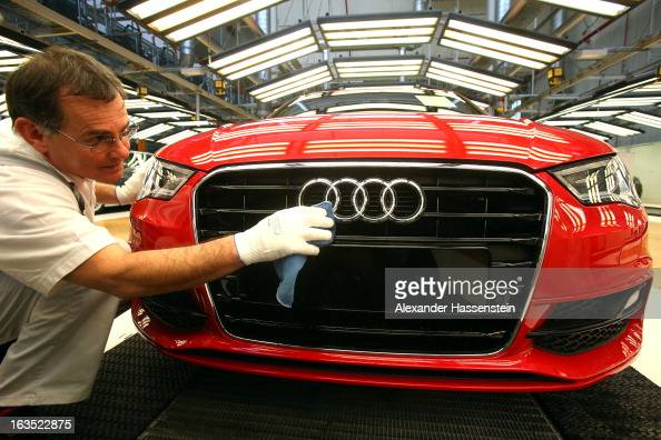 An Audi employee polishes the hood of an Audi A3 automobile produced by Volkswagen AG's Audi brand as it moves along the production line at the...