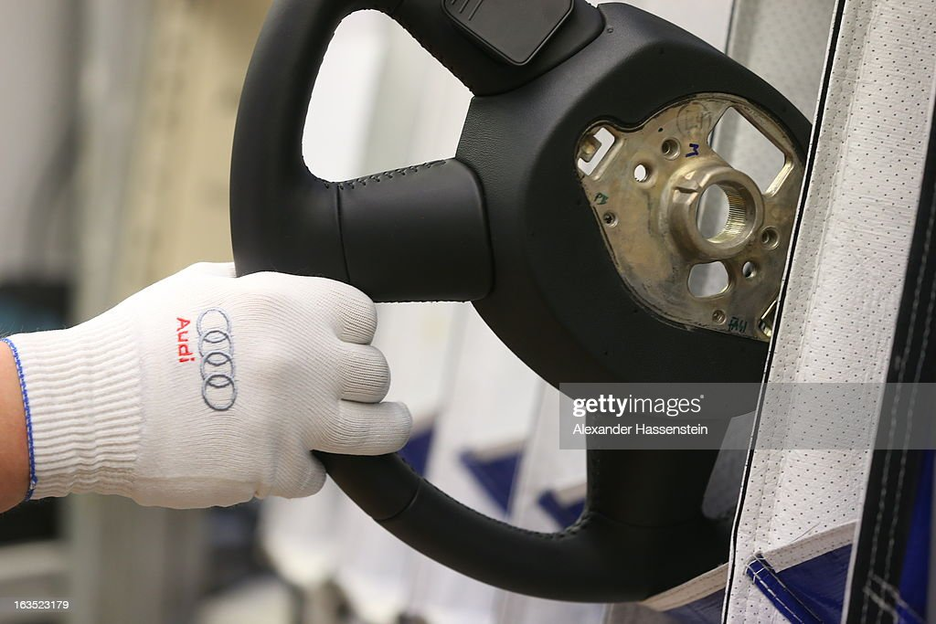 An Audi employee takes a steering wheel for a new Audi A3 automobile, produced by Volkswagen AG's Audi brand, as the unit moves along the engine production line at the company's plant in Ingolstadt, Germany, on Monday, March 11, 2013. Audi is set to spend 13 billion euros ($17 billion) through 2016 to expand and develop new cars pursuing BMW?s sales lead.