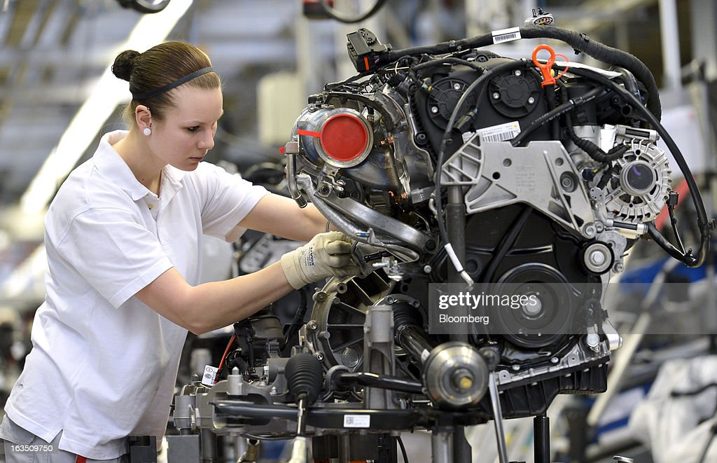 An Audi employee works on an engine for an Audi A3 automobile, produced by Volkswagen AG's Audi brand, as the unit moves along the engine production line at the company's plant in Ingolstadt, Germany, on Monday, March 11, 2013. Audi, the world's second-largest maker of luxury vehicles, plans to spend 13 billion euros ($17 billion) through 2016 to develop new cars and expand production capacity as it pursues Bayerische Motoren Werke AG's sales lead. Photographer: Guenter Schiffmann/Bloomberg via Getty Images