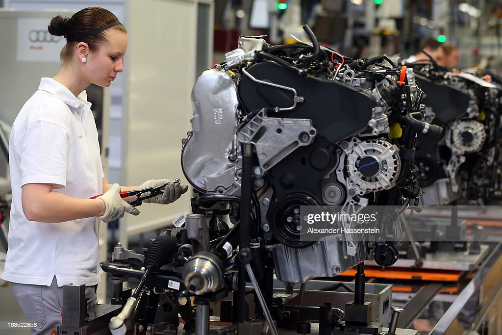 An Audi employee works on an engine for an Audi A3 automobile, produced by Volkswagen AG's Audi brand, as the unit moves along the engine production line at the company's plant in Ingolstadt, Germany, on Monday, March 11, 2013. Audi is set to spend 13 billion euros ($17 billion) through 2016 to expand and develop new cars pursuing BMW's sales lead.