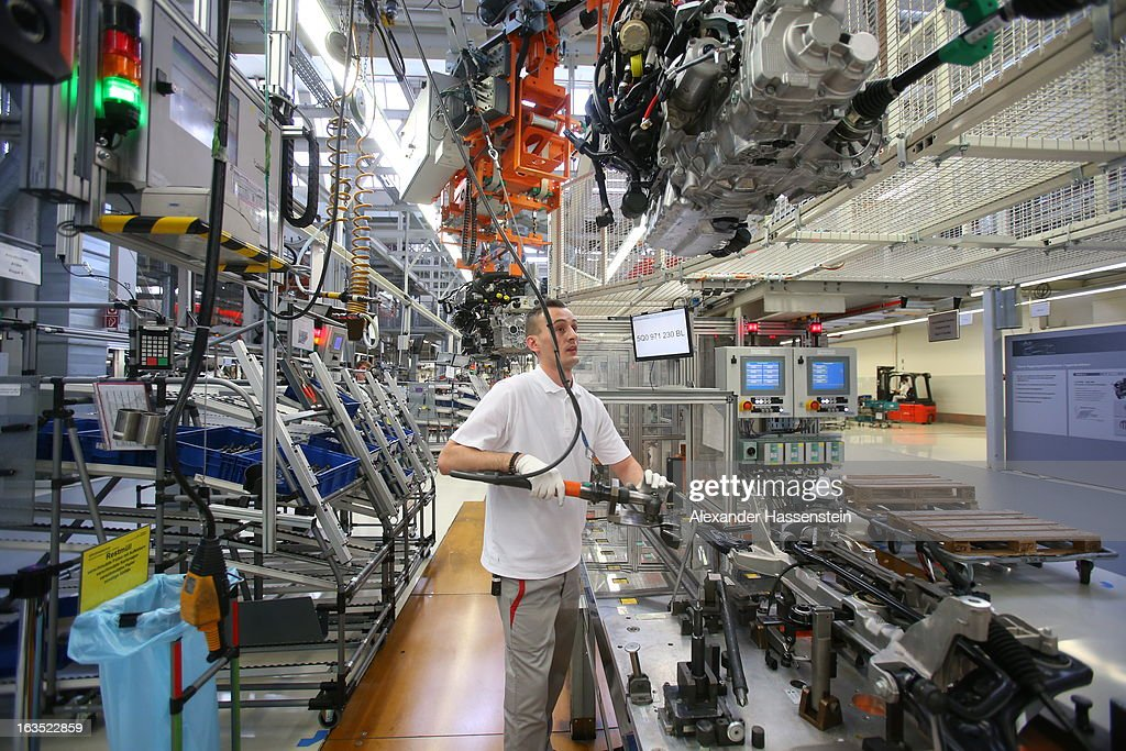 An Audi employee works on an engine for an Audi A3 automobile, produced by Volkswagen AG's Audi brand, as the unit moves along the engine production line at the company's plant in Ingolstadt, Germany, on Monday, March 11, 2013. Audi is set to spend 13 billion euros ($17 billion) through 2016 to expand and develop new cars pursuing BMW?s sales lead.