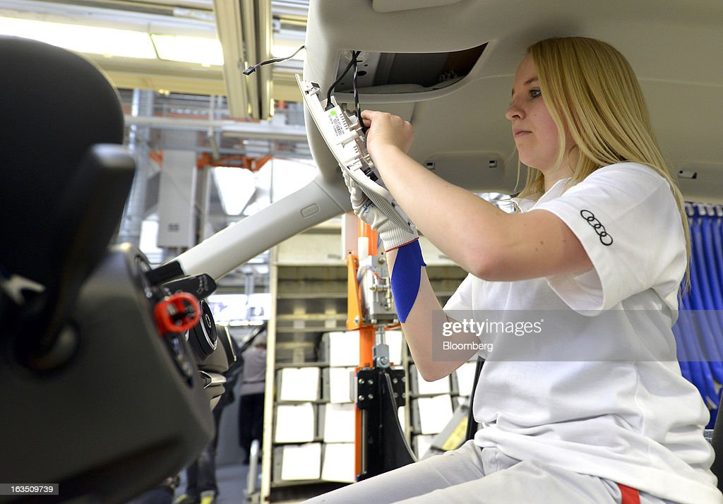 An Audi employee works on the interior of an Audi A3 automobile, produced by Volkswagen AG's Audi brand, as the vehicle moves along the production line at the company's plant in Ingolstadt, Germany, on Monday, March 11, 2013. Audi, the world's second-largest maker of luxury vehicles, plans to spend 13 billion euros ($17 billion) through 2016 to develop new cars and expand production capacity as it pursues Bayerische Motoren Werke AG's sales lead. Photographer: Guenter Schiffmann/Bloomberg via Getty Images