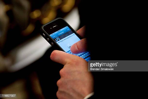 An audience member uses an iPhone to send a tweet during an online Twitter town hall meeting with US President Barack Obama from the East Room of the...