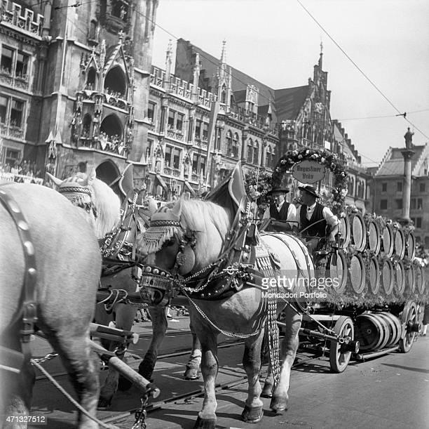 An Augustiner Brau cart loaded with casks of beer crossing Marienplatz during the Oktoberfest Munich 1951