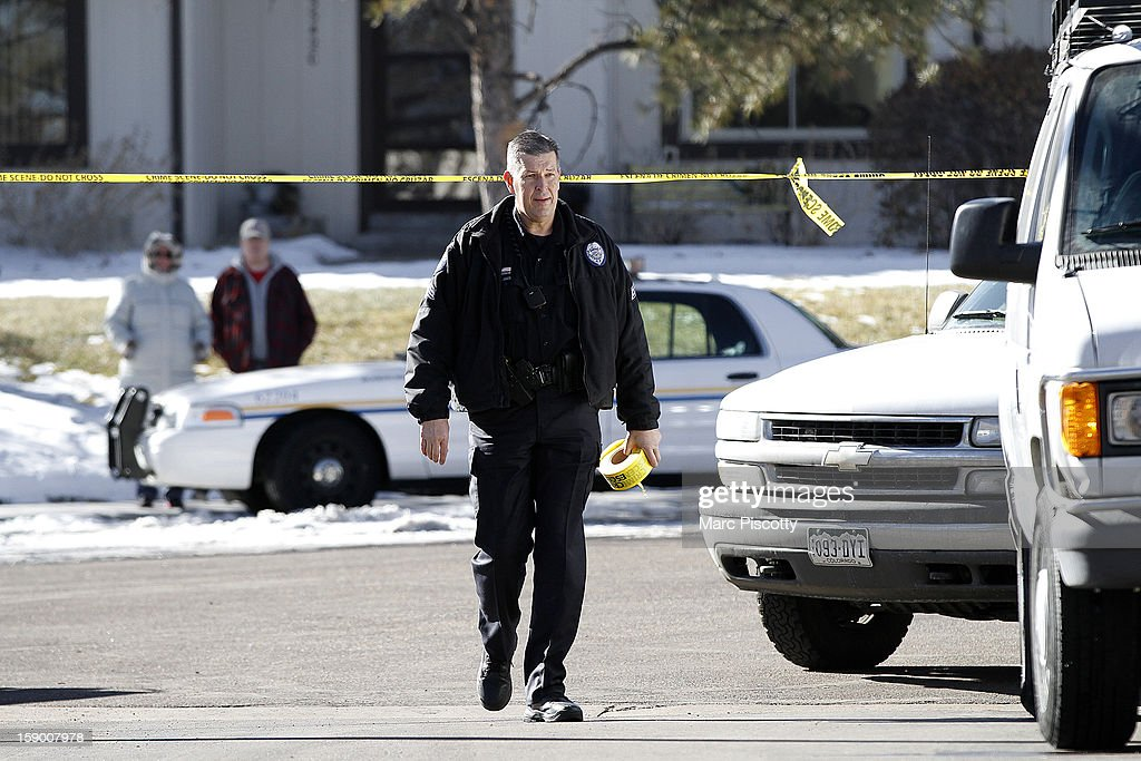 An Aurora, Colorado police officer carries crime scene tape to close off the street in front of a town home where four people were killed Saturday morning including the gunman who held police at bay for several hours at the complex January 5, 2013 in Aurora, Colorado. Aurora SWAT team members shot a gunman after he went to a second-floor window and fired at police. The gunman also allegedly fatally shot two men and a woman that he had taken hostage. One woman managed to escape from an upstairs back window, ran from the home and called police just before 3 a.m., said Cassidee Carlson, Aurora police spokeswoman.