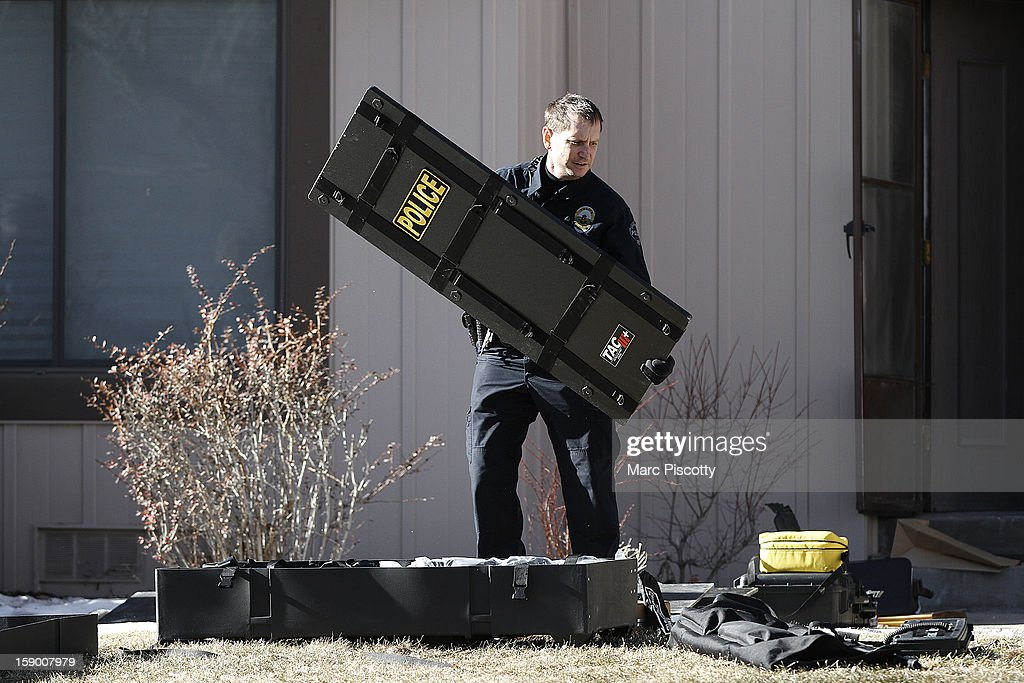 An Aurora, Colorado police officer packs up tactical gear used to subdue a gunman who killed four people at a town home complex January 5, 2013 in Aurora, Colorado. Aurora SWAT team members shot a gunman after he went to a second-floor window and fired at police. The gunman also allegedly fatally shot two men and a woman that he had taken hostage. One woman managed to escape from an upstairs back window, ran from the home and called police just before 3 a.m., said Cassidee Carlson, Aurora police spokeswoman.