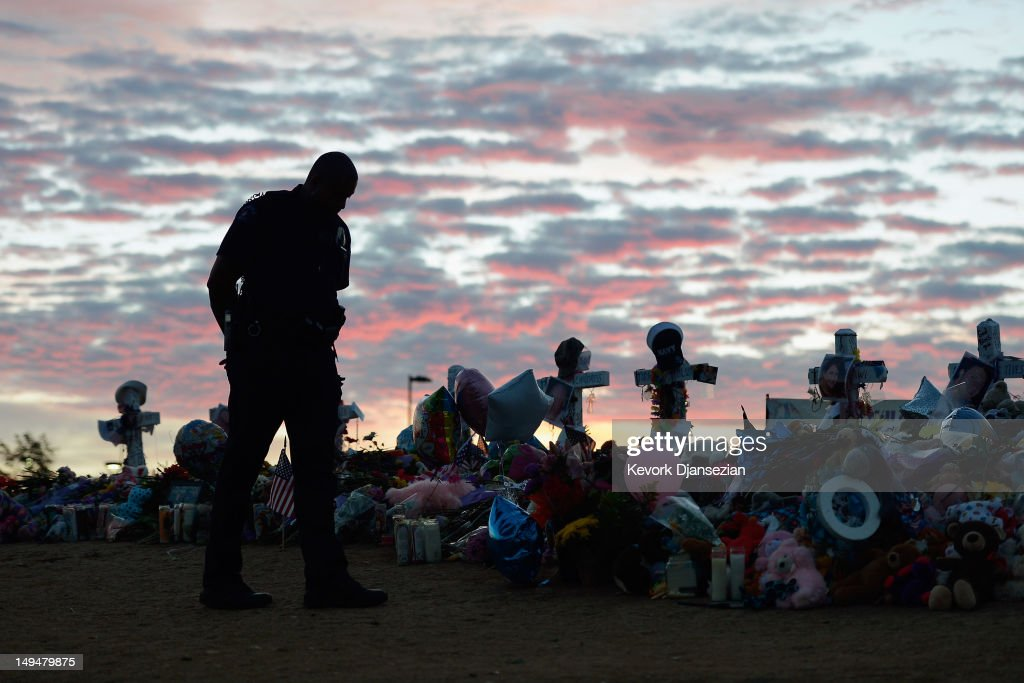 An Aurora, Colorado Police officer visits the roadside memorial set up for victims of the theaters shooting massacre across the street from Century 16 movie theater at sunrise July 29, 2012 in Aurora, Colorado. Twenty-four-year-old James Holmes is suspected of killing 12 and injuring 58 others on July 20 during a shooting rampage at a screening of 'The Dark Knight Rises' in Aurora, Colorado.