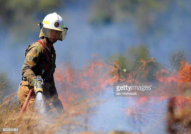 An Australian army firefighter puts out a small bushfire which was started during an Army fire power demonstration at Range Control High Range on...