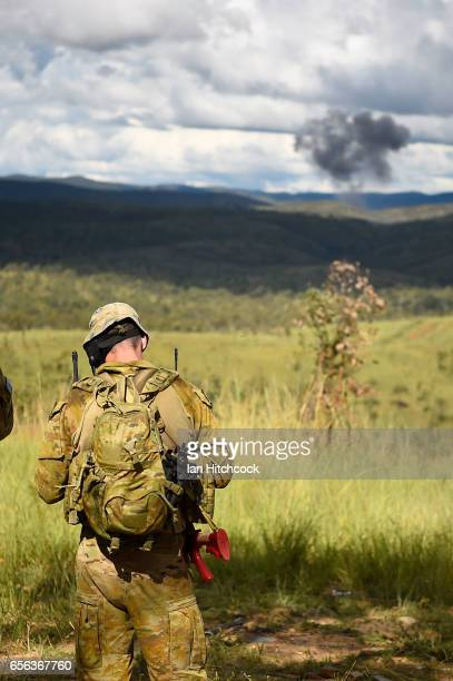 An Australian Army JTAC member checks his maps after the detonation of a high explosive bomb in the distance on March 22 2017 in Townsville Australia...