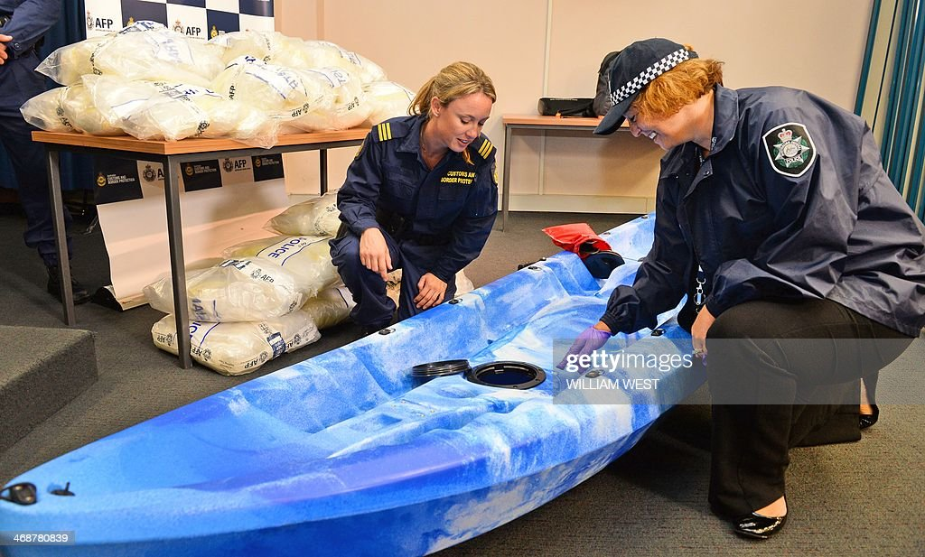 An Australian Customs officer (C) and a Australian Federal Police officer (R) inspect one of the 27 kayaks seized after Australian authorities found Aus$180 million (US$162 million) of methamphetamine stashed in a consignment of kayaks from China, in Sydney on February 12, 2014. Four Taiwanese nationals were arrested afte the 183-kilogramme (402-pound) haul was discovered during a joint Australian Federal Police and Customs and Border Protection Service operation at Sydney's container port. AFP PHOTO / William WEST