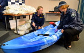 An Australian Customs officer and a Australian Federal Police officer inspect one of the 27 kayaks seized after Australian authorities found Aus$180...