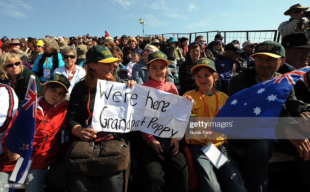 An Australian family displays a banner reading as 'We're here grandpa and poppy' during a service held at the Australian Lone Pine monument on April...