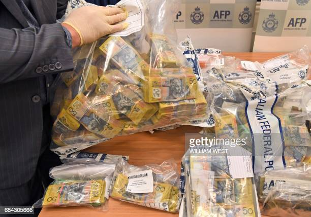 An Australian Federal Police officer displays some of the cash found after they smashed a massive fraud syndicate and seized planes guns and luxury...