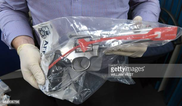 An Australian Federal Police officer handles one of the many guns found after they smashed a massive fraud syndicate and seized planes guns and...
