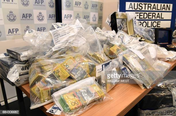 An Australian Federal Police officer handles some of the cash found after they smashed a massive fraud syndicate and seized planes guns and luxury...
