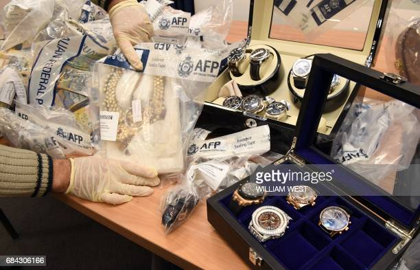 An Australian Federal Police officer handles some of the jewellery found after they smashed a massive fraud syndicate and seized planes guns and...
