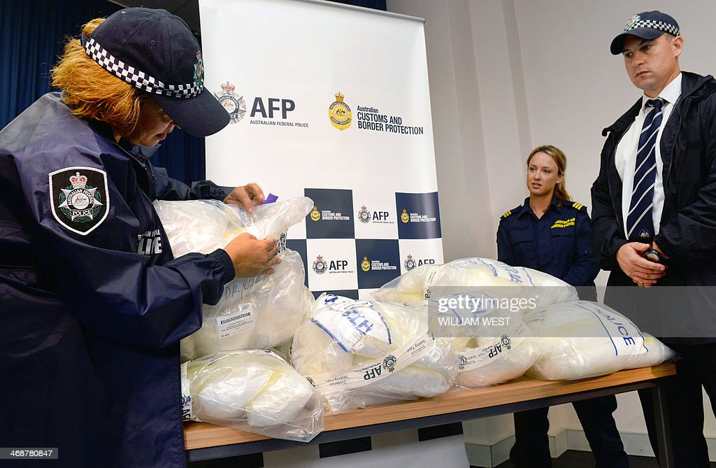 An Australian Federal Police officer (L) inspects seized methamphetamine after Australian authorities found Aus$180 million (US$162 million) of the drug stashed in a consignment of kayaks from China, in Sydney on February 12, 2014. Four Taiwanese nationals were arrested afte the 183-kilogramme (402-pound) haul was discovered during a joint Australian Federal Police and Customs and Border Protection Service operation at Sydney's container port. AFP PHOTO William WEST