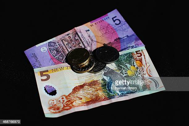 An Australian five dollar banknote a New Zealand five dollar bank note and New Zealand coins are arranged for a photo on April 7 2015 in Auckland New...