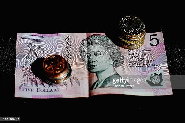 An Australian five dollar banknote and New Zealand coins are arranged for a photo on April 7 2015 in Auckland New Zealand The New Zealand dollar...