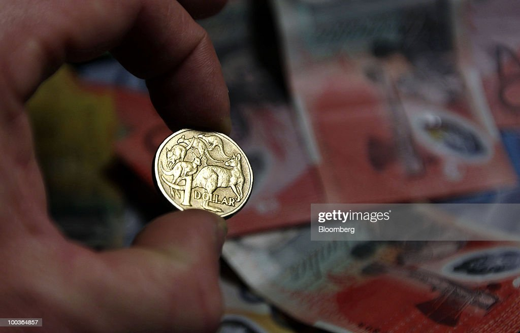 An Australian one-dollar coin is displayed in front of banknotes in various denominations, in Sydney, Australia, on Monday, May 24, 2010. The Australian and New Zealand currencies slid for the sixth time in seven days against the U.S. dollar on concern Europe's debt crisis will spread. Photographer: Ian Waldie/Bloomberg via Getty Images