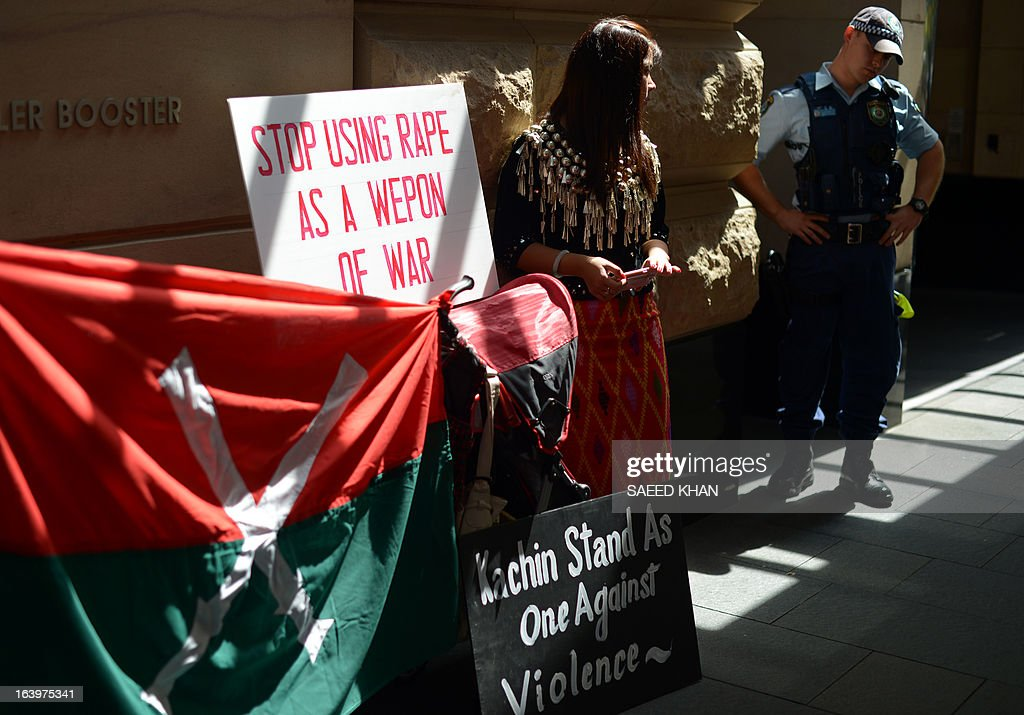 An Australian police officer (R) stands guard next to a Myanmar activist during a protest against the Myanmar army in front of the Australia Department of Foreign Affairs and Trade (DFAT) in Sydney on March 19, 2013. Scores of Myanmar activists gathered in front of the DFAT and demanded Australian government to take a strong stance against ongoing human rights abuses in Myanmar and to condemn military attacks in Kachin state in northern Myanmar and ethnic violence against ethnic Rohingya Muslims. President Thein Sein is visiting Australia from 17 to 20 March and is the first by a head of state of Myanmar since 1974. AFP PHOTO / Saeed Khan