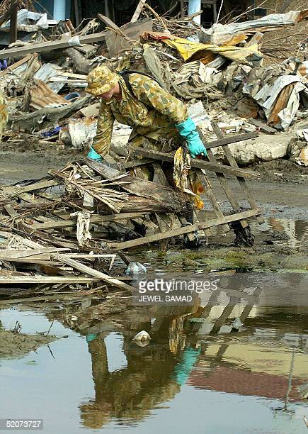 An Australian soldier cleans debris from a tsunami devastated street in Banda Aceh 28 January 2005 The December 26 quake and tsunamis left about...